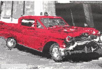 Ciekawy motyw czerwonego auta na tle budynku.