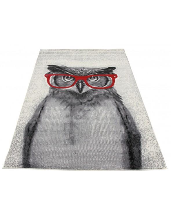 Na dywanie przedstawiona jest sowa w okularach na jasnym tle.