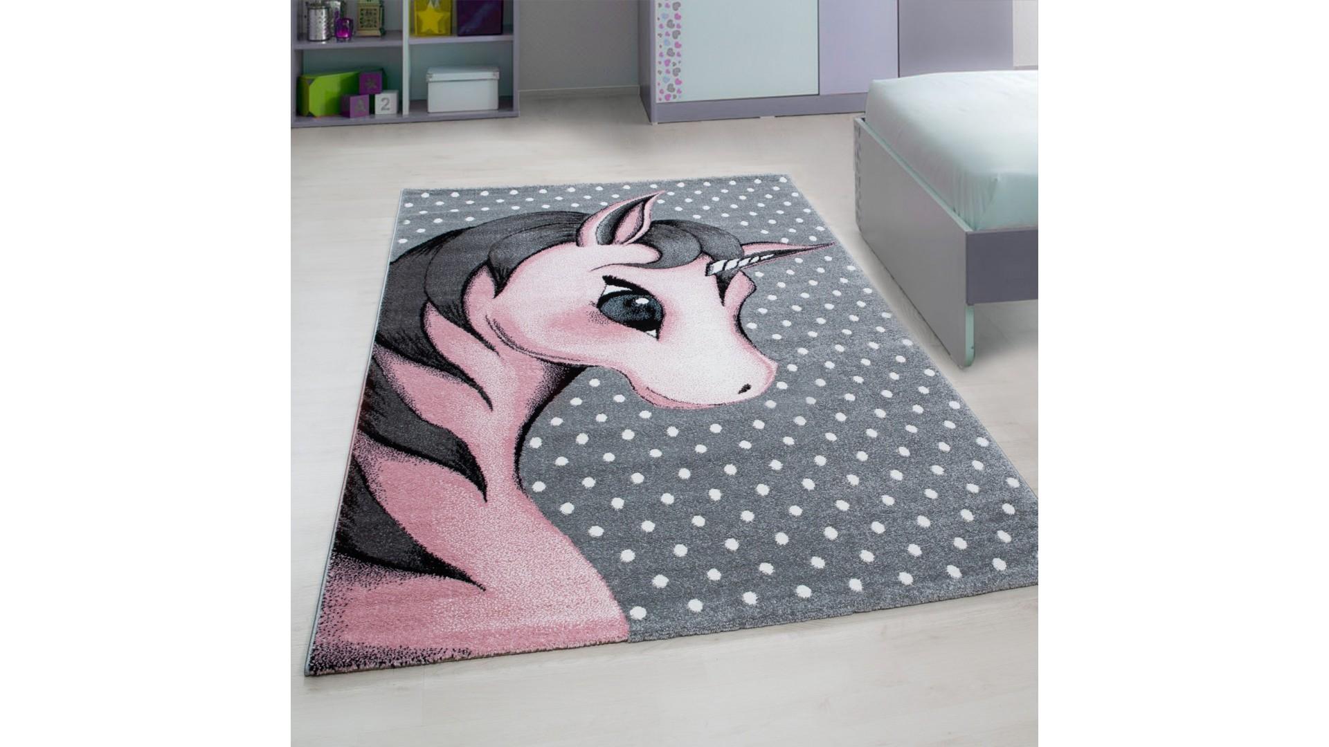 Przepiękny różowy jednorożec umieszczony w rogu dywanu.